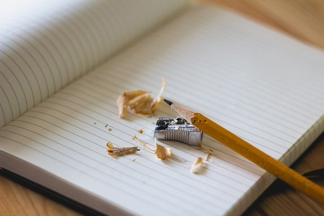 A pencil and pencil sharpener on a notebook